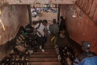 Young man looking at trainers on improvised shoe stall. Bandjoun Market, Pete area. © Yvon Ngassam.